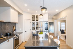 Calypso showhome in Jensen Lakes. Kitchen design with abstract grey and white counters accented with gold trimmed interior design and solver appliances.