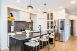 The Calypso showhome by Pacesetter homes in Jensen Lakes St. Albert. Kitchen with grey and white countertops modern gold and white design and accent wine wall.