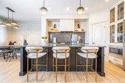 Gold trimmed kitchen with black stone countertops and gold interior modern design in St. Albert. Pacesetter Calypso showhome in Jensen Lakes.
