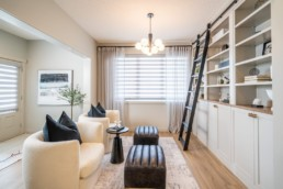 Pacesetter Homes Calypso showhome in Jensen Lakes St. Albert. Lifestyle room with white chairs and decoration ladder to interior designed modern shelves and large windows.