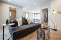 Pacesetter homes showhome loft with grey couches and spacious living area in Jensen Lakes.