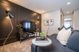 Calypso showhome loft with black wall and wire tv stand and side tables. Dark grey interior design in Jensen Lakes St. Albert.