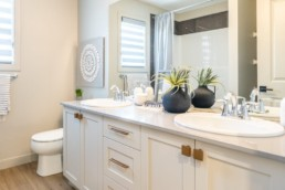 Bathroom with two sinks and white cabinets, accented with gold and hardwood floor in Pacesetter Calypso showhome in Jensen Lakes St. Albert.