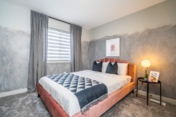 Secondary kids bedroom with abstract grey walls geometric bedding and cloth pink bedframe. Jensen Lakes Pacesetter Homes in St. Albert.