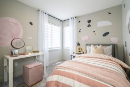 Girls bedroom with pink bed spread and pink decor accents. Located in Pacesetter showhomes in Jensen Lakes St. Albert.